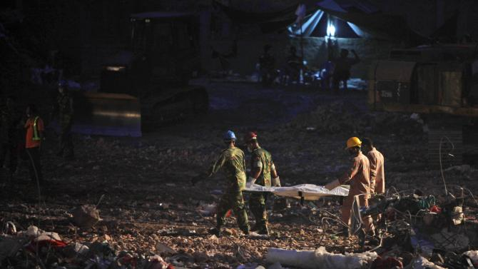 Rescuers carry the body of a victim retrieved from the rubble of the site of a garment factory that collapsed in Savar, near Dhaka, Bangladesh, Saturday, May 11, 2013. The death toll from Bangladesh's worst industrial disaster is more than 1,000 and climbing. More than 2,500 people were rescued in the immediate aftermath of the April 24 disaster. (AP Photo/A.M. Ahad)