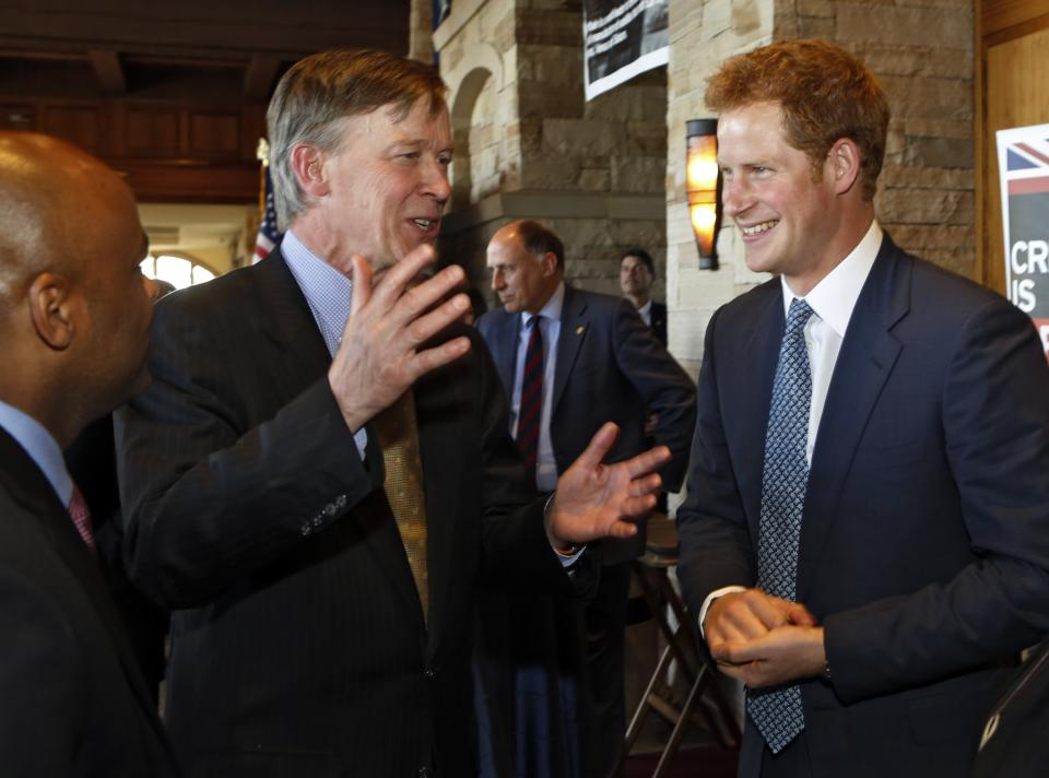 Britain's Prince Harry, right, listens to Colorado Gov. John Hickenlooper, center, at a reception at the Sanctuary Golf Course in Sedalia, Colo., south of Denver on Friday, May 10, 2013. Denver Mayor John Hancock is pictured at left. (AP Photo/Ed Andrieski, Pool)