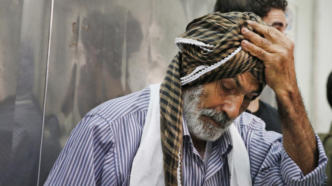 Palestinian Ahmed Jadallah, 75, takes a break as he prepares a body for burial at the morgue of Kamal Adwan hospital in Beit Lahiya, northern Gaza Strip, Thursday, July 24, 2014. Over the past three decades, the 75-year-old Jadallah has dressed hundreds of 'martyrs' _ those killed in conflict with Israel. He said his volunteer work fulfills an Islamic commandment and that he hopes it will earn him a place in paradise. (AP Photo/Lefteris Pitarakis)