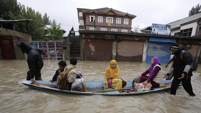 Residents leave a flooded neighborhood on a boat in Srinagar, India, Thursday, Sept. 4, 2014. Authorities say heavy rains have triggered floods and landslides in the Indian portion of Kashmir, killing at least 14 people in the worst flooding in 22 years. (AP Photo/Mukhtar Khan)