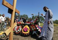 A priest conducts a funeral ceremony, while acquaintances of Pyotr Ostapenko, 35, a flood victim, stand nearby, at the central cemetery in Krymsk in theKrasnodar region, southern Russia, July 9, 2012. Russia began a day of mourning on Monday for the 171 people killed in floods that drove thousands from their homes, with the causes of the disaster posing hard questions for the authorities, including President Vladimir Putin.  REUTERS/Eduard Korniyenko  (RUSSIA - Tags: DISASTER ENVIRONMENT POLITICS OBITUARY RELIGION)
