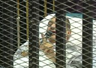 This video image taken from Egyptian State Television showing 83-year-old former Egyptian president Hosni Mubarak speaks to the court, using a microphone while laying on a hospital bed inside a cage of mesh and iron bars in a Cairo courtroom Wednesday Aug. 3, 2011,  as his historic trial began on charges of corruption and ordering the killing of protesters during the uprising that ousted him from office.  The scene, shown live on Egypt's state TV, was Egyptians' first look at their former president since Feb. 10, the day before his fall when he gave a defiant speech refusing to resign. (AP Photo/Egyptian State TV)   EGYPT OUT