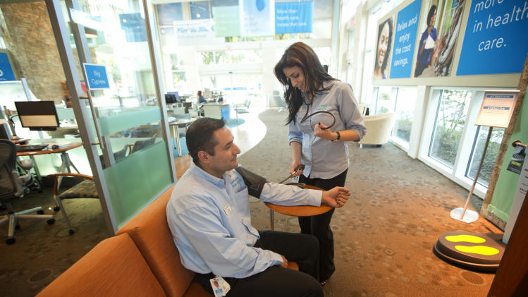 In this Thursday, Feb. 7, 2013 photo,Yolanda Hormilla, a RN working for Florida Blue, checks Jose Ballivian's blood pressure in the Sunrise, Fla. sales office. Some Americans could see their insurance costs double this year as the U.S. health care overhaul expands coverage to millions of people. (AP Photo/J Pat Carter)