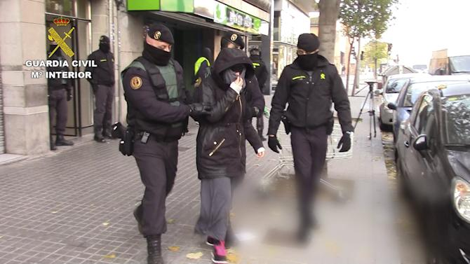 Spanish Interior Ministry handout shows Spanish police escorting a woman suspected of recruiting fighters for the Islamic State in Granollers, near Barcelona