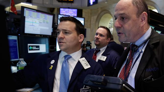 Specialist Paul Cosentino, left, works at his post on the floor of the New York Stock Exchange Wednesday, March 20, 2013. Stocks are opening higher on Wall Street as the European island nation of Cyprus seeks alternatives to a bailout plan its legislature overwhelmingly rejected the day before. (AP Photo/Richard Drew)