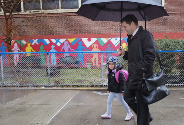 Matthew Mosca takes his daughter, Ella, to her kindergarten class at Public School 33, Wednesday, Jan. 16, 2013 in New York. Mosca said his 5-year-old usually takes the bus from their home on Manhatta