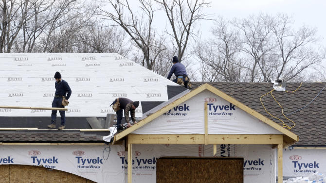 In this Friday, March 21, 2014 photo, roofers install a roof on a new construction home in Pepper Pike, Ohio. The Commerce Department releases new home sales for February, on Tuesday, March 25, 2014. (AP Photo/Tony Dejak)