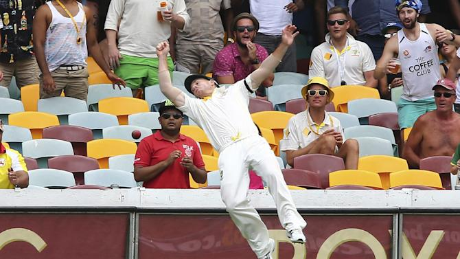 Australia's David Warner dives over the boundary rope trying to take a catch during their play on day four of the second cricket test in Brisbane, Australia, Saturday, Dec. 20, 2014. (AP Photo/Tertius Pickard)