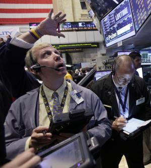 FILE - In this Tuesday, July 31, 2012 file photo, trader Richard Cohen, left, works on the floor of the New York Stock Exchange. The rating agency Standard & Poor's stunned the world a year ago by stripping the U.S. government of its prized AAA bond rating. A year later, S&P's historic move looks like a non-event. Long-term interest rates are sharply lower, the Dow Jones industrial average has reversed course and is now up more than 1,600 points. The dollar has rallied, and gold prices are down from where they were when S&P lowered the boom (AP Photo/Richard Drew, File)