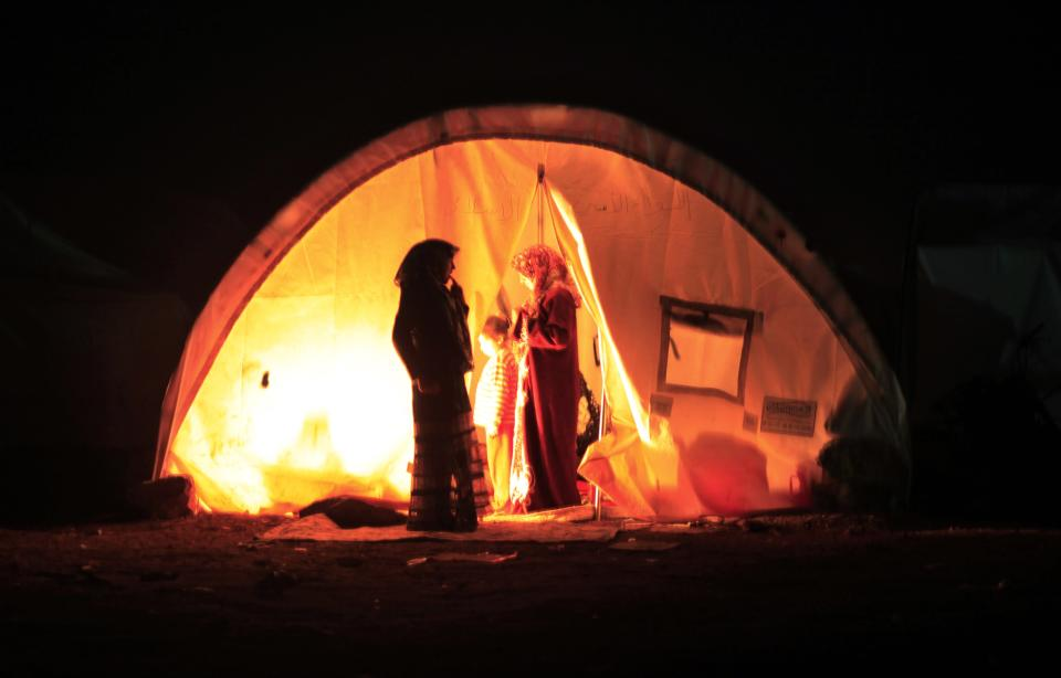 A Syrian family who fled the violence in their village, set up a fire inside their tent at a camp in the Syrian village of Atma, near the Turkish border with Syria, Sunday, Nov. 4, 2012.(AP Photo/Khalil Hamra)