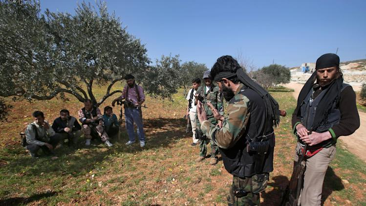 A Free Syrian Army fighter Abu al-Yaman, second right, a commander of Knights of the North brigade, gives his instruction to his fighters as they prepare to reconnaissance a Syrian army forces base of al-Karmid, at Jabal al-Zaweya, in Idlib province, Syria, Wednesday, Feb. 27, 2013. Syrian warplanes carried out airstrikes on rebels trying to storm a police academy outside Aleppo on Wednesday, while jihadi fighters battled government troops along a key supply road leading to the southeastern part of the city, activists said. (AP Photo/Hussein Malla)