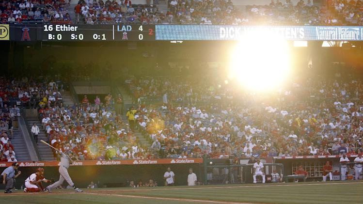 Los Angeles Dodgers' Andre Ethier, left, hits a single as sunlight comes through the stadium in the second inning of the Dodgers' baseball game against the Los Angeles Angels in Anaheim, Calif., Friday, June 22, 2012. (AP Photo/Jae C. Hong)