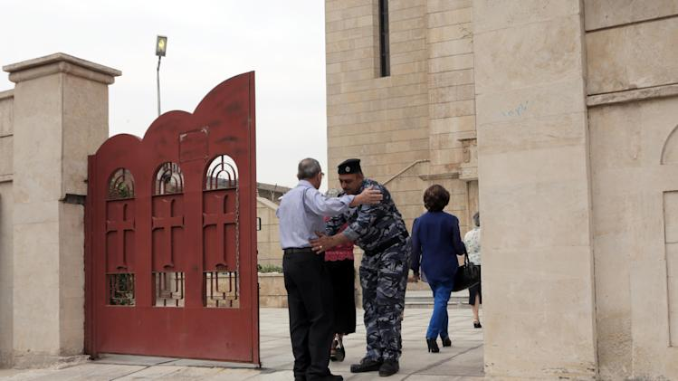 A policeman searches a man outside Our Lady of flowers Catholic church during the celebration of Easter in Baghdad, Iraq, Sunday, April 20, 2014. Iraq's dwindling Christian community, which is estimated to number about 400,000 to 600,000 people, has often been targeted by al-Qaida and other insurgents. (AP Photo/Khalid Mohammed)