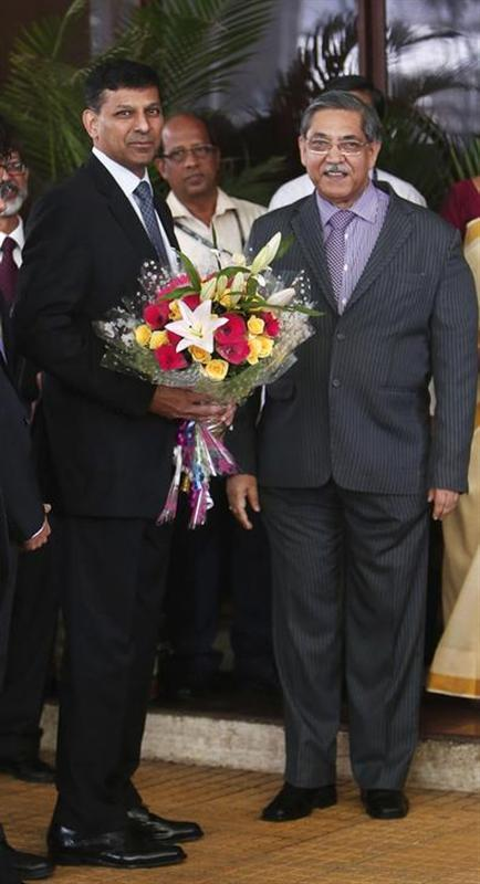Raghuram Rajan, newly appointed governor of Reserve Bank of India (RBI), receives a bouquet from the RBI deputy governor K C Chakrabarty after his arrival at the bank's headquarters in Mumbai September 4, 2013. REUTERS/Danish Siddiqui