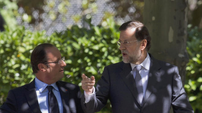 French President Francois Hollande, left  and Spain's Prime Minister Mariano Rajoy walk in the gardens before a meeting at the Moncloa Palace in Madrid Thursday Aug. 30, 2012.  Hollande met Rajoy for talks on Spain's economic crisis and the future of the euro. (AP Photo/Paul White)