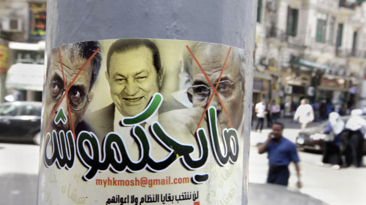 "Egyptians walk near a poster showing ousted president Hosni Mubarak, center, and presidential candidates Amr Moussa, left, Mubarak's foreign minister for 10 years, and Ahmed Shafiq, a former Air Force commander and civil aviation minister whom Mubarak made prime minister during his last days in power, with Arabic that reads, ""they will not rule,"" in Cairo, Egypt, Monday, May 21, 2012. The May 23-24 presidential election is the first since last year's ouster of longtime authoritarian ruler Hosni Mubarak. It marks the first time Egyptians will choose their leader in a race overseen by international monitors. (AP Photo/Amr Nabil)"