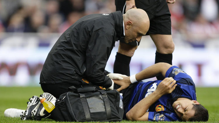 Manchester United's Javier Hernandez grimaces after being injured colliding with Stoke City's Jonathan Woodgate during their English Premier League soccer match at the Britannia Stadium, Stoke, England, Saturday Sept. 24, 2011. (AP Photo/Jon Super)