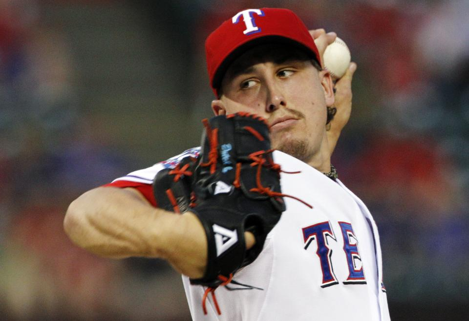 Texas Rangers' Derek Holland delivers to the Oakland Athletics in the first inning of a baseball game, Monday, Sept. 24, 2012, in Arlington, Texas. (AP Photo/Tony Gutierrez)