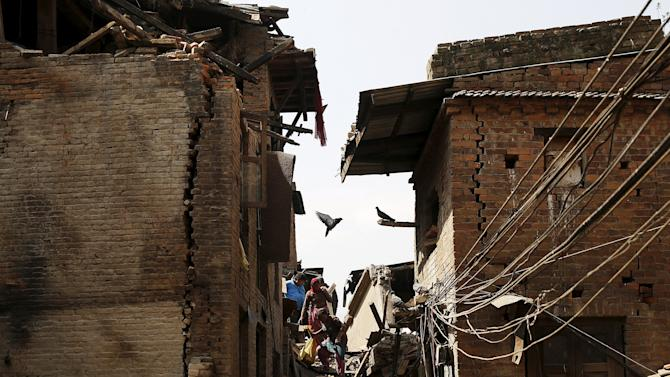 People walk though the rubble left after earthquake in Bhaktapur, Nepal