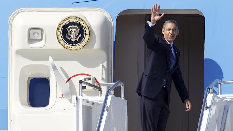 President Barack Obama waves prior to boarding Air Force One before leaving Seattle ,Wednesday July 25, 2012. . (AP Photo/Stephen Brashear)