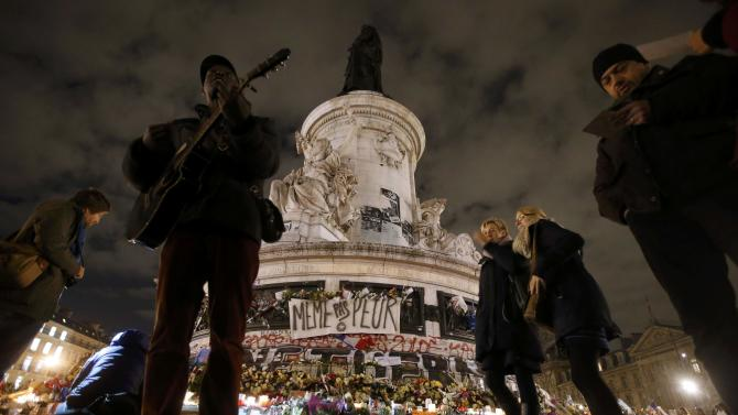 """A guitarist, who gave his name as Ghitobe, sings the """"Marseillaise"""", the French national anthem, by the statue at the Place de la Republique on the eve of a ceremony to pay tribute for the victims of shooting attacks in Paris"""