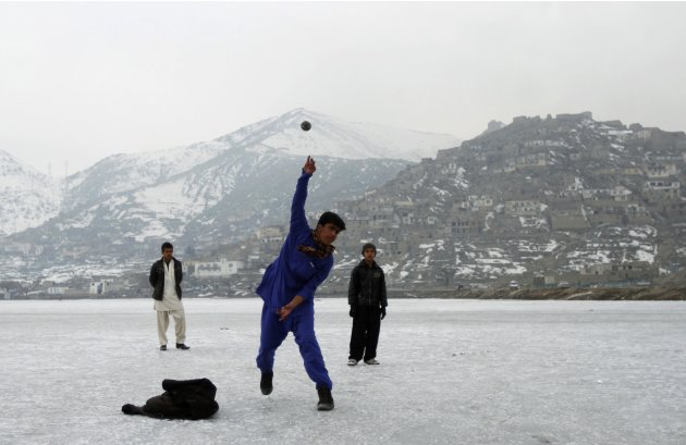 An Afghan boy throws a cricket ball on a frozen lake in Kabul