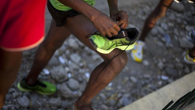"In this Jan. 6, 2013 photo, Astrel Clovis, a 42-year-old marathon runner, laces his running shoes, in preparation for the ""Let's Go Haiti,"" race, organized in honor of those who died in the 2010 earthquake in Port-au-Prince, Haiti.  Like virtually all Haitians in the capital of 3 million, the runner's life was disrupted by the catastrophic earthquake on Jan. 12, 2010. Six days a week, the rail-thin athlete sets off at daybreak, wearing his second-hand, neon-green running shoes. In a country where good health is a luxury, running keeps Clovis strong. He clocks about 75 miles (120 kilometers) a week. (AP Photo/Dieu Nalio Chery)"