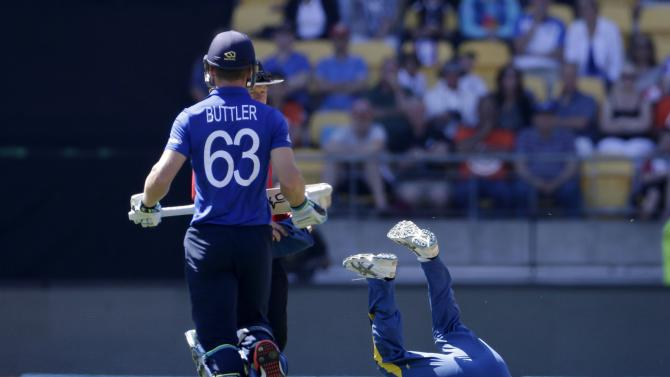 Sri Lanka's Rangana Herath rolls on the ground after injuring a finger while fielding a shot from England's Jos Buttler during their Cricket World Cup match in Wellington