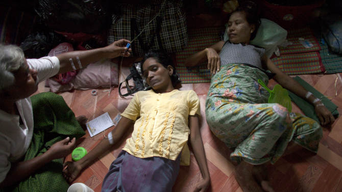 In this Sept. 1, 2012 photo, an HIV-infected woman, center, receives medication through an intravenous drip after she fainted, as another HIV patient, right, is also treated in a hut shared with other HIV patients at an HIV/AIDS hospice on the outskirts of Yangon, Myanmar. According to UNAIDS, AIDS kills an estimated 18,000 people a year in Myanmar. The country is one of the hardest places in the world to receive HIV treatment. Myanmar spent less than $1 per person on health in 2008, minus donor money, and ranks among the lowest countries in nearly every category of health care funding. Now, with the dramatic change that has given Myanmar an elected government, there are hopes for improvement, but the country faces a long climb. (AP Photo/Alexander F. Yuan)