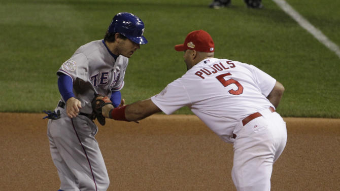 St. Louis Cardinals first baseman Albert Pujols tags out Texas Rangers' Ian Kinsler as he is caught stealing during the first inning of Game 7 of baseball's World Series Friday, Oct. 28, 2011, in St. Louis. (AP Photo/Paul Sancya)