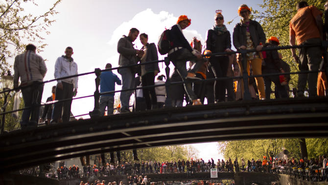 People celebrate In their boats sailing along a canal as others stand on bridges in Amsterdam, The Netherlands, Tuesday April 30, 2013. Around a million people are expected to descend on the Dutch capital for a huge street party to celebrate the first new Dutch monarch in 33 years. (AP Photo/Emilio Morenatti)