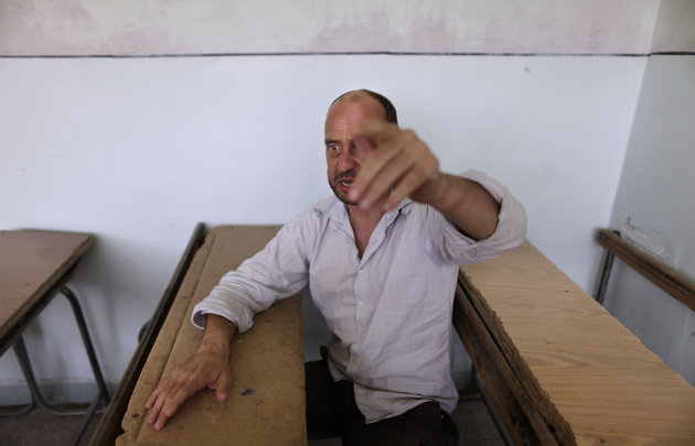 In this Friday, Aug. 24, 2012 photo, Syrian prisoner, Mohammed Abeid, 42, gestures while talking at a makeshift prison run by rebels in a former elementary school in Al-Bab on the outskirts of Aleppo, Syria. Many improvised detention centers have sprung up as rebels wrest cities from army control, but these facilities fall under no national or regional authority, causing concern among rights groups. (AP Photo/Muhammed Muheisen)