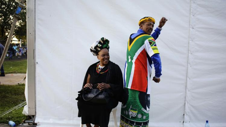 People pose as they wait for a bus to pay their respects to former South African President Mandela in Pretoria