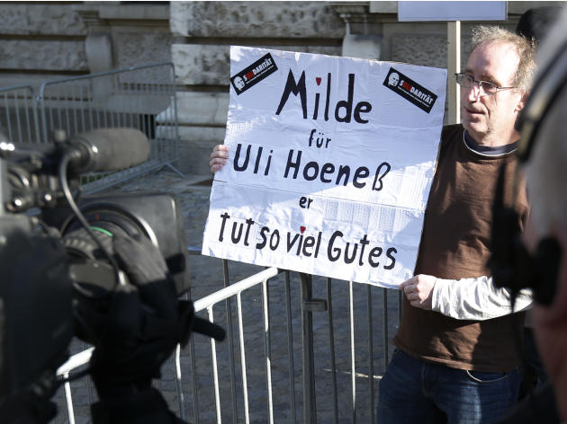 Supporter of Bayern Munich President Hoeness awaits the arrival of Hoeness outside the regional court in Munich