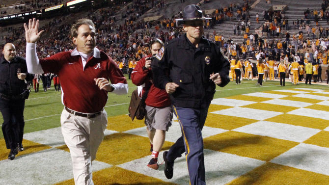 Alabama head coach Nick Saban, front left, waves as he leave the field after an NCAA college football game against Tennessee, Saturday, Oct. 20, 2012, in Knoxville, Tenn. Alabama won 44-13. (AP Photo/Wade Payne)