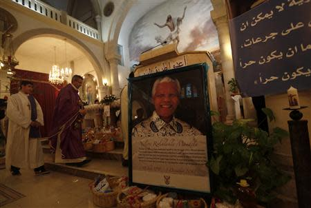 A poster depicting former South African President Mandela is displayed during a special service in his honour at the Holy Family Church in the West Bank city of Ramallah
