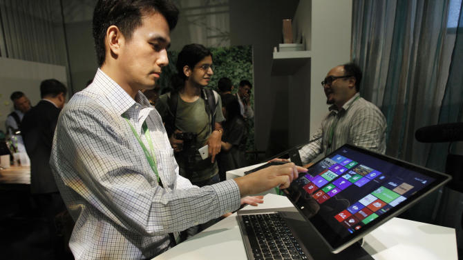 An Acer employee displays a new tablet-laptop hybrid Aspire R7 at an international press conference on the eve of the opening of Computex, one of the world's largest IT exhibitions, in Taipei, Taiwan, Monday, June 3, 2013. Aspire R7 features a hinge-attached pad that holds up the touchscreen and allows users to pull the screen closer or flip it over the keyboard, transforming it into a tablet. (AP Photo/Wally Santana)