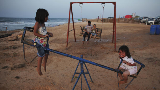Libyan children play on a see-saw on a beach in Tripoli, Libya, Wednesday, July 20, 2011. The White House says it is up to the Libyan people to decide whether longtime leader Moammar Gadhafi can stay in Libya if he steps down from power. White House spokesman Jay Carney says the U.S. continues to believe that Gadhafi has lost legitimacy and needs to give up power. (AP Photo/Tara Todras-Whitehill)