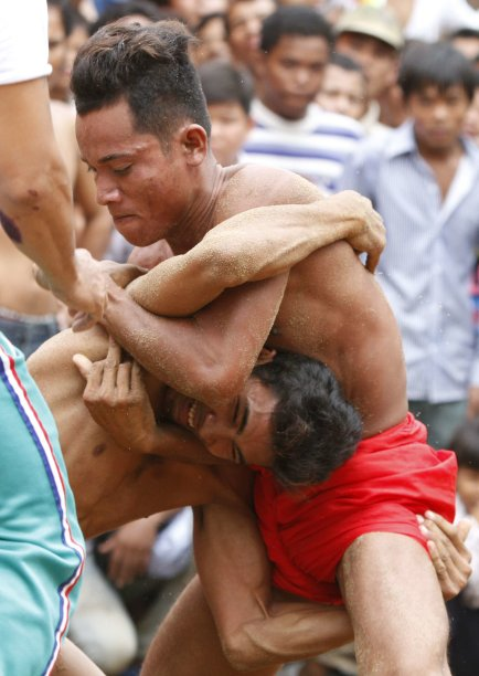 Men wrestle during an annual buffalo-racing ceremony at Virhear Sour village in Kandal province