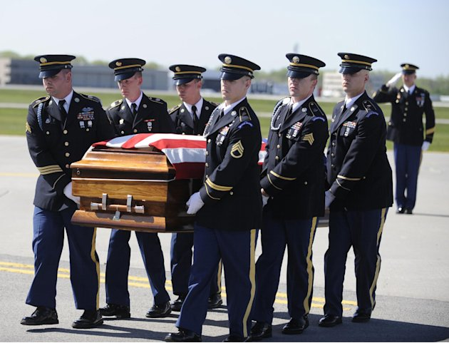 The body of U.S. Army nurse Capt. Bruce Kevin Clark who died in Afghanistan, carried across the tarmac during Military honors at Rochester International Airport Saturday, May 12, 2012. Military offici