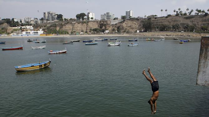 A boy jumps from a dock at Pescadores beach in Chorrillos district of Lima