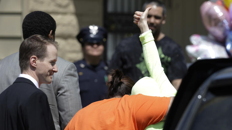 Gina DeJesus, one of three women held captive for about a decade at a run-down Cleveland house, gives a thumbs-up as she is escorted toward her home Wednesday, May 8, 2013, in Cleveland. The miraculous rescue of the three missing women has given hope to many families whose loved ones have vanished. Yet hope, when searching for a long-lost child, can be a dangerous thing. (AP Photo/Tony Dejak)