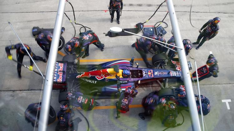 Crew members works on a Red Bull car of Sebastian Vettel from Germany at the pit during the Malaysian Formula One Grand Prix at Sepang, Malaysia, Sunday, March 24, 2013. (AP Photo/Vincent Thian)