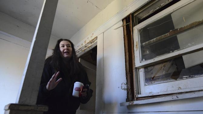 Jane Bryant stands in a stairwell of the apartment building where Lee Harvey Oswald lived from November 1962 to March 1963 in Dallas, Thursday, Nov. 29, 2012. The apartment complex in the Oak Cliff area is in the process of being demolished. Bryant is under a court order to raze the structure.  (AP Photo/Benny Snyder)
