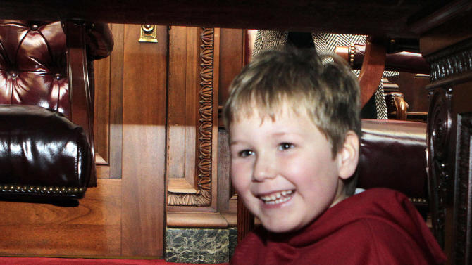 In this photo provided by the Governor's office, six-year-old Ethan Gilman plays under the table during a visit to the Governor's Office in Montgomery, Ala. on Wednesday, Feb. 13, 2012. Ethan was held hostage in an underground bunker in a near week-long standoff in Midland City, Ala. (AP Photo/Alabama Governor's Office, Jamie Martin)