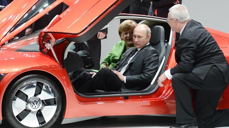 Russian president Vladimir Putin, center, and German chancellor Angela Merkel, left,  sit in XL1 Volkswagen car next to  VW CEO Martin Winterkorn right, at the opening tour at the Hannover Fair in Hannover, Germany, Monday April 8, 2013.  (AP Photo/dpa, Jochen Luebke)