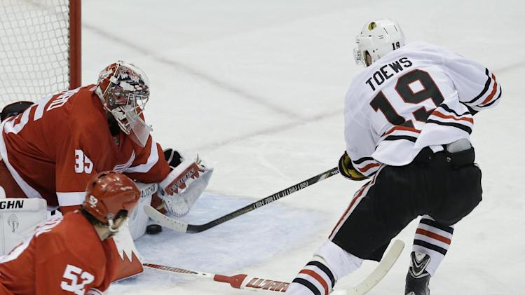 Detroit Red Wings goalie Jimmy Howard (35) stops a Chicago Blackhawks center Jonathan Toews (19) shot during the second period in Game 6 of the Western Conference semifinals in the NHL hockey Stanley Cup playoffs in Detroit, Monday, May 27, 2013. (AP Photo/Paul Sancya)