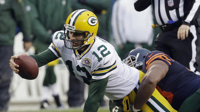 Green Bay Packers quarterback Aaron Rodgers (12) is tackled by Chicago Bears defensive end Corey Wootton in the second half of an NFL football game in Chicago, Sunday, Dec. 16, 2012. The Packers won 21-13 to clinch the NFC North division title. (AP Photo/Nam Y. Huh)