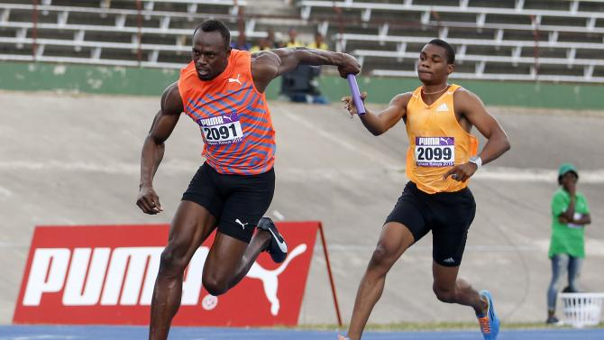 Jamaica's Usain Bolt receives the baton from Warren Weir while participating in his first race of the season during the Gibson Relays in Kingston