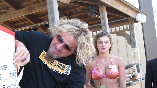Singer Sammy Hagar signs the actual $10,000 check he donated on May 18, 2012 to a church food pantry in Atlantic City, leaning it on top of a large ceremonial check at his beach bar on the Atlantic City Boardwalk. Hagar told The Associated Press he's not surprised the Van Halen tour appears to be crumbling, with dozens of dates postponed. (AP Photo/Wayne Parry)
